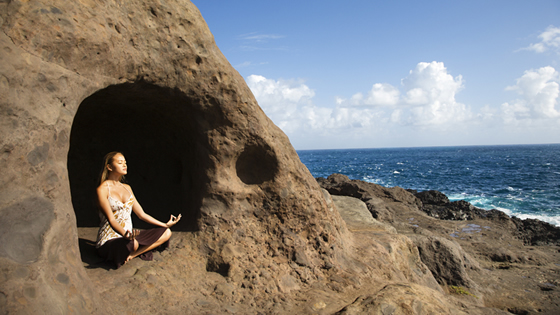 Young Woman Meditating in Cave